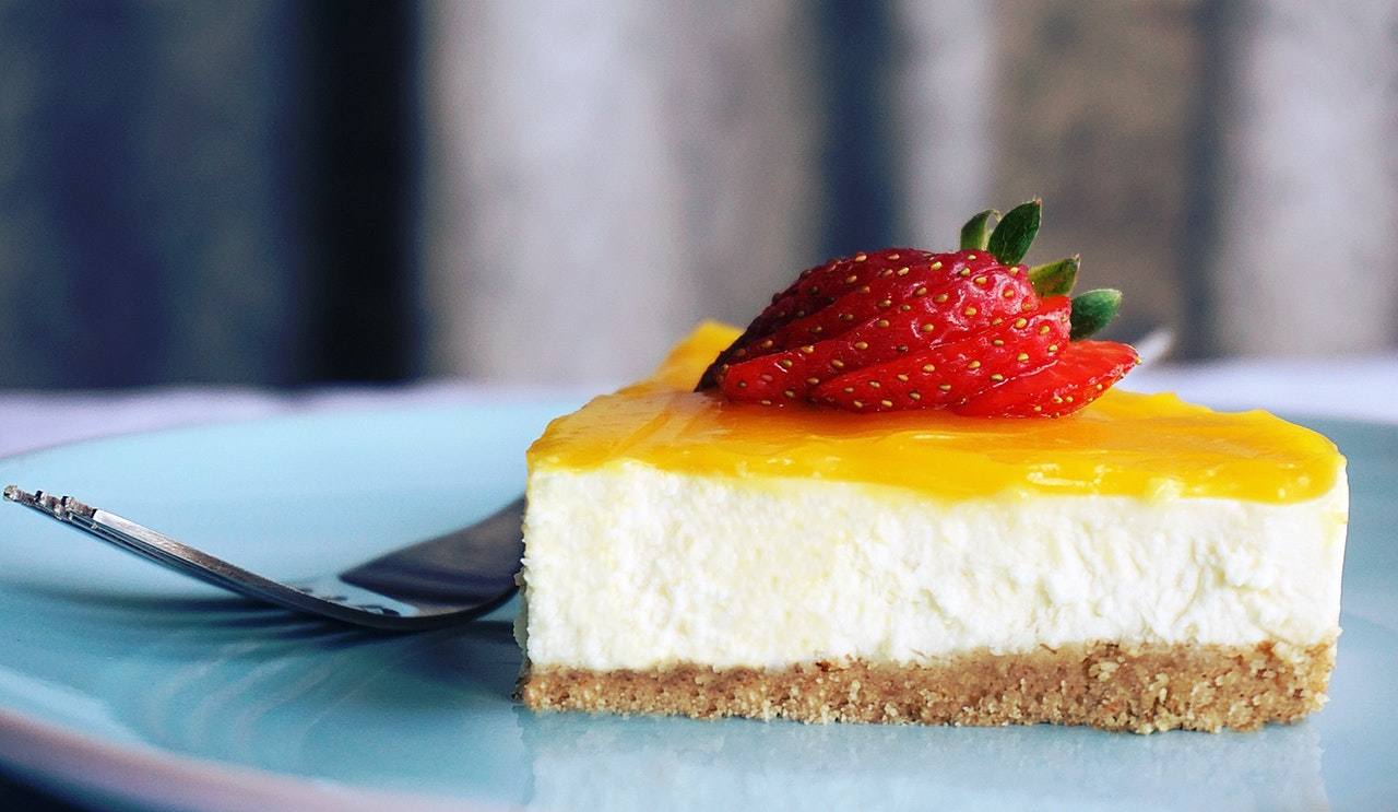 mango cheese cake topped with fresh and sliced strawberry