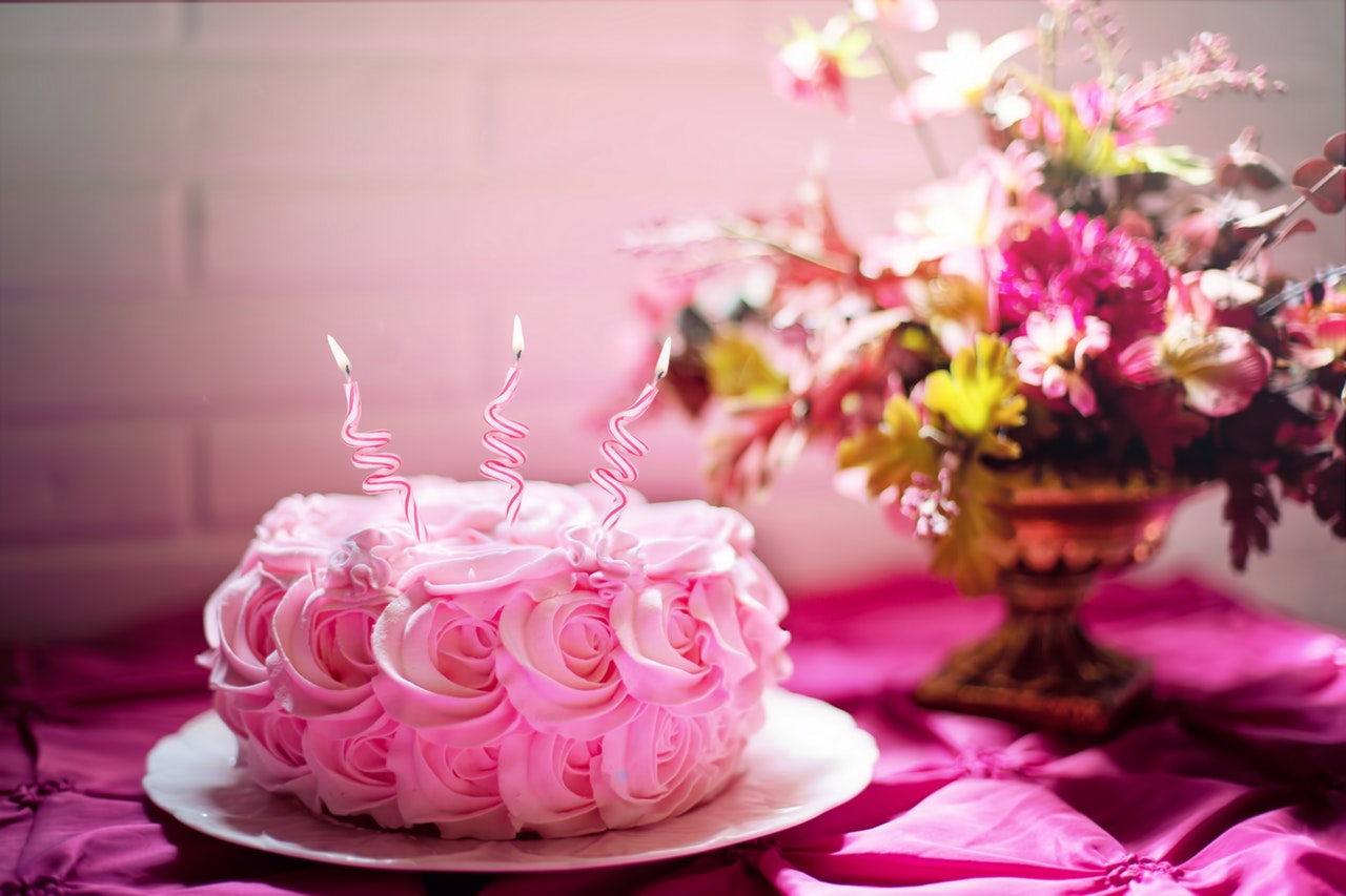 A Beautifully Decorated Pink Cake With Three Lit Candles On Top Of The Table And Right